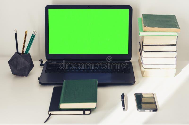 Grön skärmbärbar dator, bunt av böcker, anteckningsbok och blyertspennor på den vita tabellen, bakgrund för utbildningskontorsbeg royaltyfri fotografi