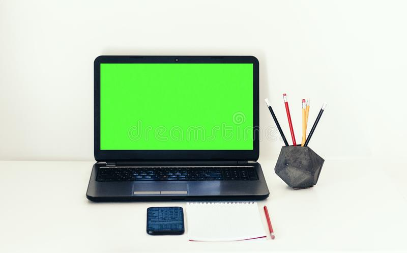 Grön skärmbärbar dator, smartphone, anteckningsbok och blyertspennor i konkret hållare på den vita tabellen, bakgrund för utbildn arkivbilder