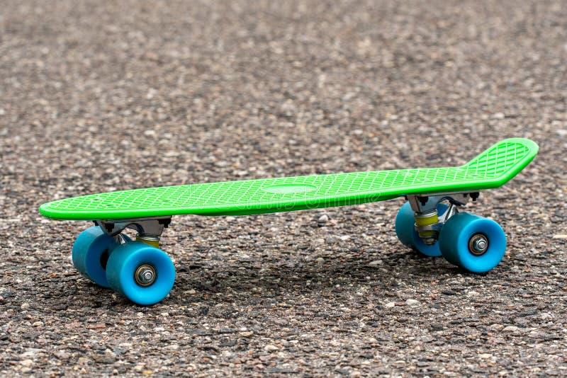 Grön skateboard på vägen royaltyfri fotografi