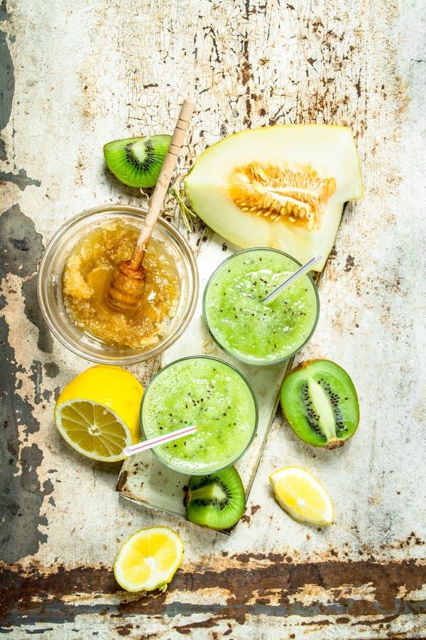 Grön smoothie av kiwin, melon och citronen med honung royaltyfria bilder