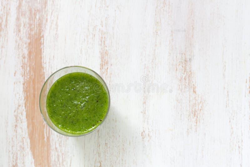 Grön smoothie i exponeringsglas arkivbilder