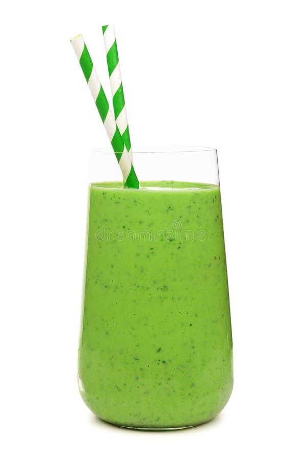 Grön smoothie i exponeringsglastorktumlare med pappers- sugrör som isoleras på vit fotografering för bildbyråer