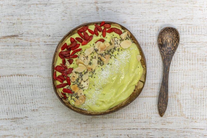 Grön smoothie i kokosnötbunke med avokadot, röda gojibär, mandelflingor, kokosnötchiper och chiafrö för frukosten, slut royaltyfria bilder