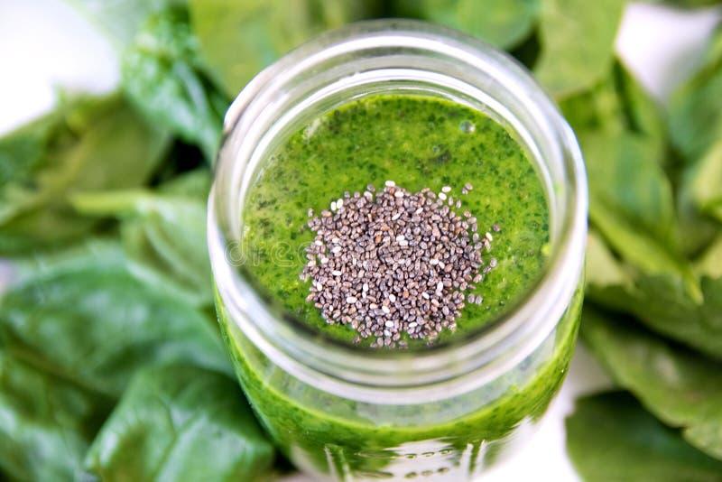 Grön smoothie i krus, uppe i luften på exponeringsglas, sund drink med grönsaksidor, bakgrund royaltyfria bilder