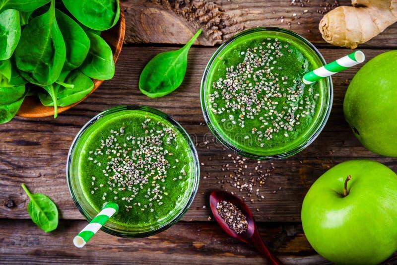 Grön smoothie med spenat-, äpple-, ingefära- och chiafrö på en träbakgrund Top beskådar royaltyfri fotografi