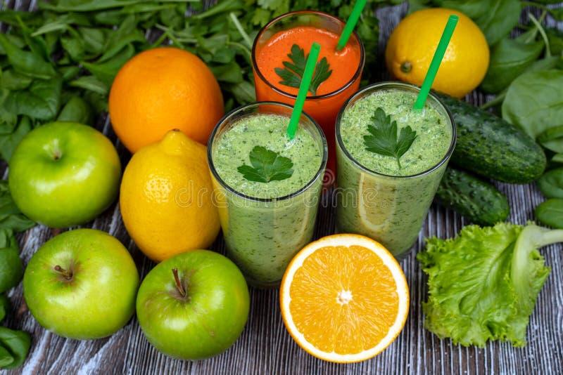 Grön smoothie, morotfruktsaft och mångfärgad frukt, gröna Apple, gurka, spenat, citron, apelsin, sallad, koriander arkivfoto