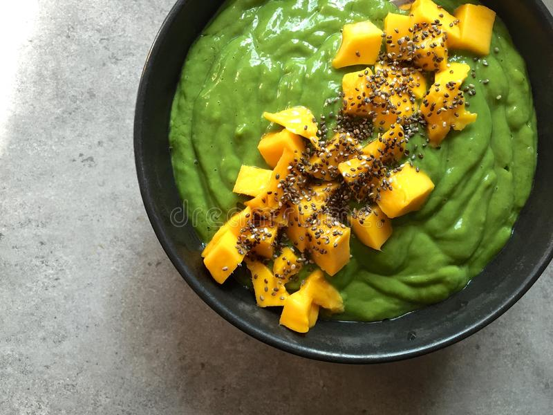 Grön smoothiebunke med huggit av mango- och chiafrö arkivfoto