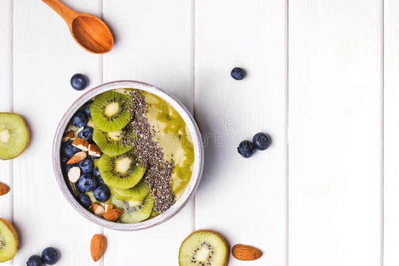 Grön smoothiebunke med kiwi-, blåbär- och chiafrö arkivbilder