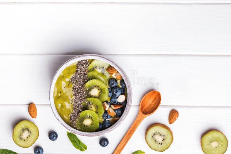 Grön smoothiebunke med kiwi-, blåbär- och chiafrö fotografering för bildbyråer