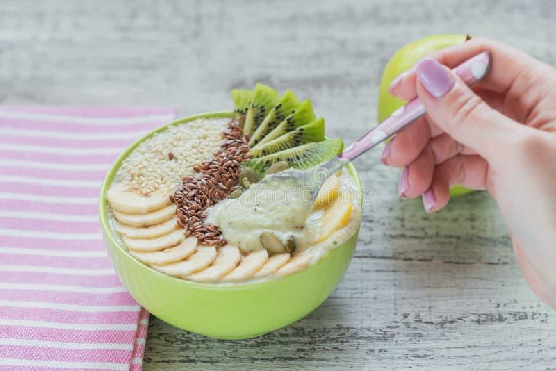 Grön smoothiebunke som överträffas med kiwi, banan, äpplen och frö f arkivfoton