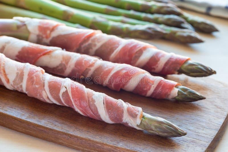 Gr?n sparris och bacon p? ett tr?br?de, ingredienser f?r sund aptitretare som ?r horisontal royaltyfria foton