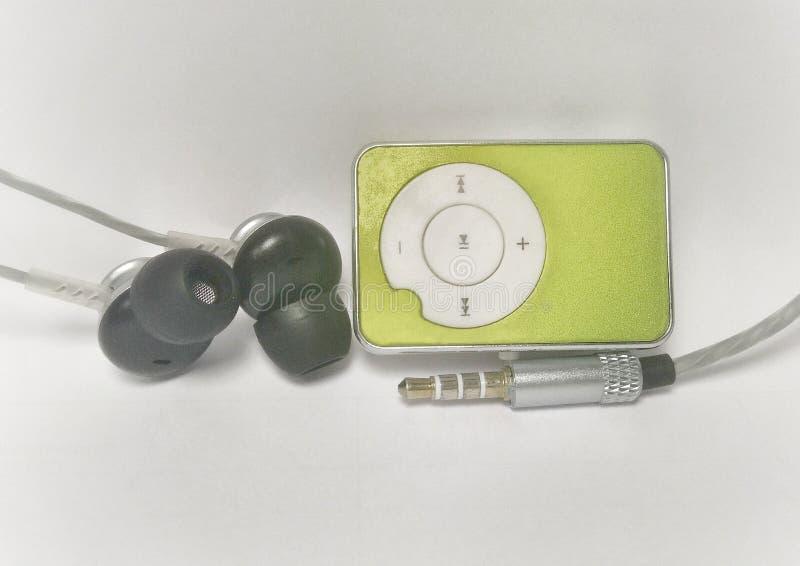 Grön spelare mp3 med en hörlur och en ljudsignal stålar arkivfoton