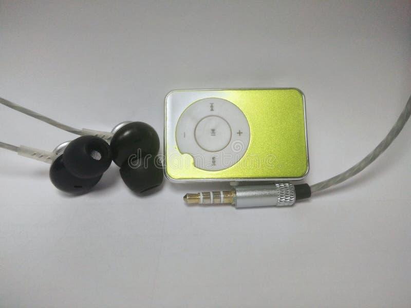 Grön spelare mp3 med en hörlur och en ljudsignal stålar royaltyfri fotografi