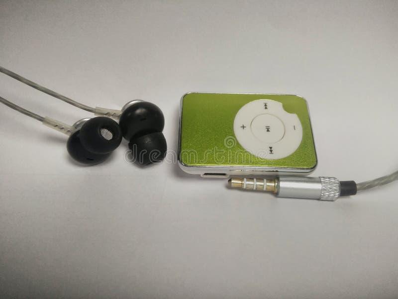 Grön spelare mp3 med en hörlur och en ljudsignal stålar arkivbild