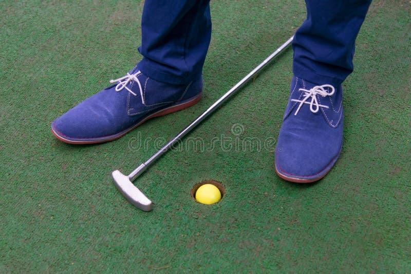 Grön sportbakgrund, mini- golfbana, en boll i facket och en pinne royaltyfri bild