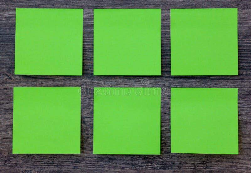 Grön stolpe som den noterar på den wood bakgrunden royaltyfri fotografi