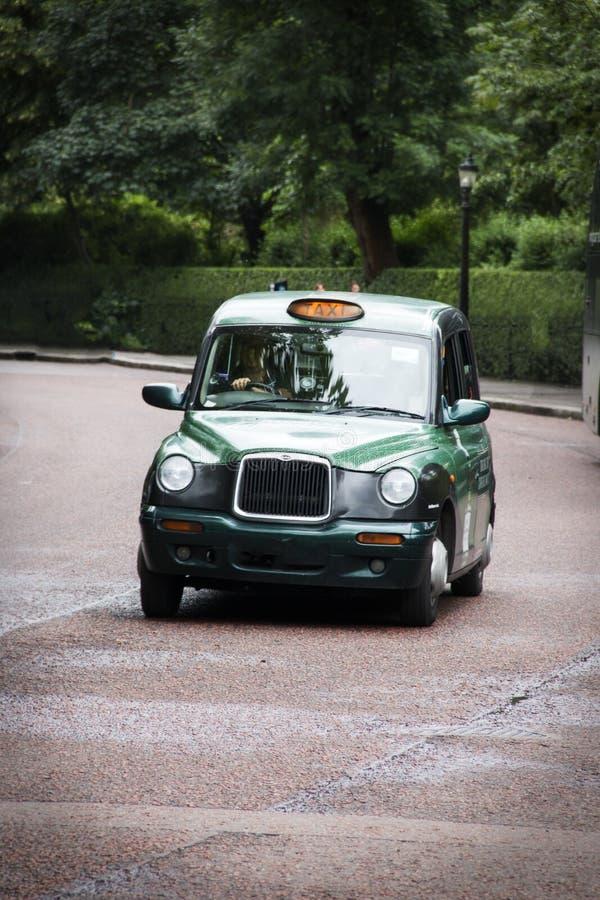 Grön taxitaxi i London England royaltyfri fotografi