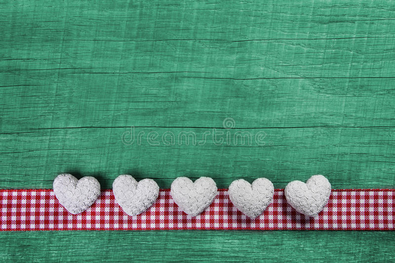 Grön träbakgrund med hjärtor på en röd vit kontrollerad ram arkivbilder