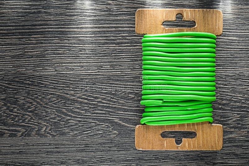 Grön trädgårds- bandtråd på träbräde arkivbilder