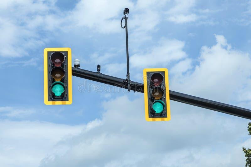 Grön trafikljus på den hängande lampan under himmel arkivbild
