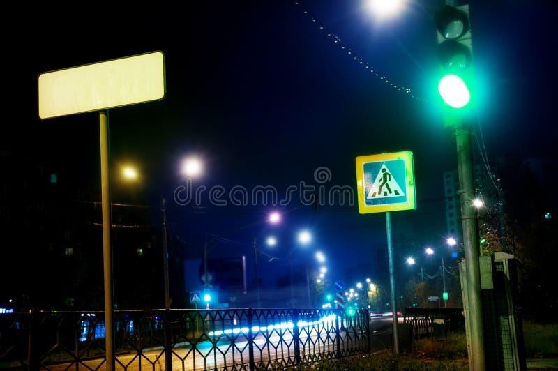 Grön trafikljus på natten, övergångsställe i staden på gatan royaltyfria foton