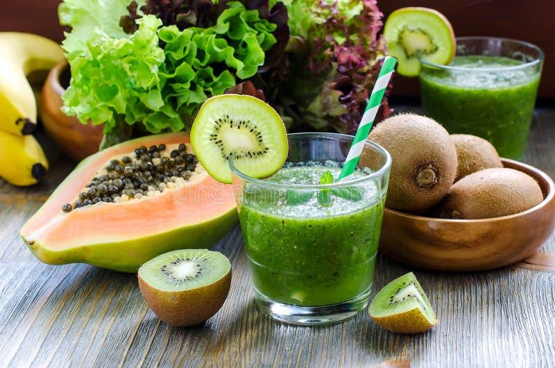Grön tropisk smoothie med kiwi-, papaya- och salladsidor fotografering för bildbyråer