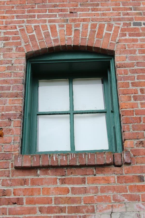 Grön vägg för tegelsten för fönsterram arkivbilder