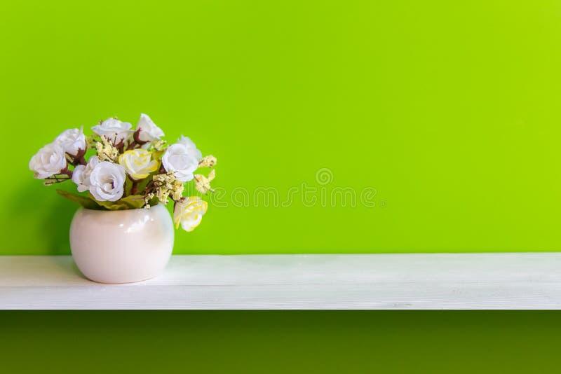Grön vägg med blommor på vitt trä för hylla, kopieringsutrymme för prov arkivbild
