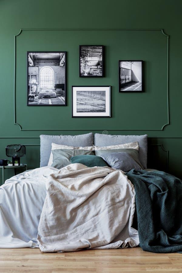 Grön vägg med gallerit av affischen i det moderiktiga sovrummet som är inre med dubbelsäng royaltyfria bilder