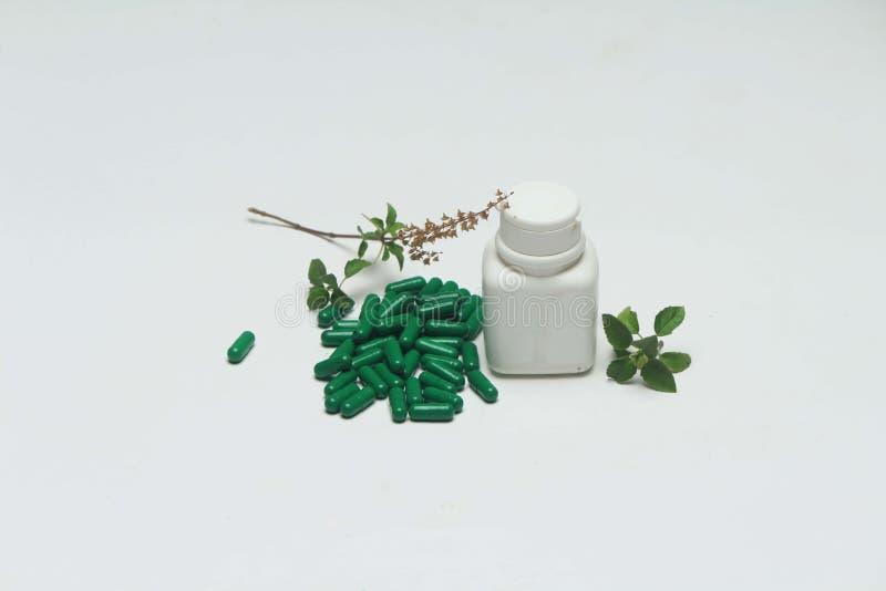 Grön vitaminkapsel, flaska och basilikasidor royaltyfri foto