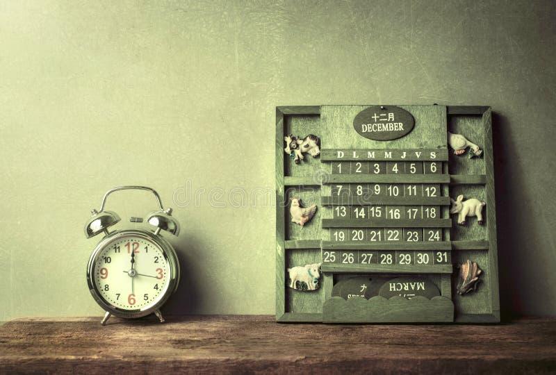 grön wood kalendertappning och ringklocka på det wood tabellslutet av arkivfoton