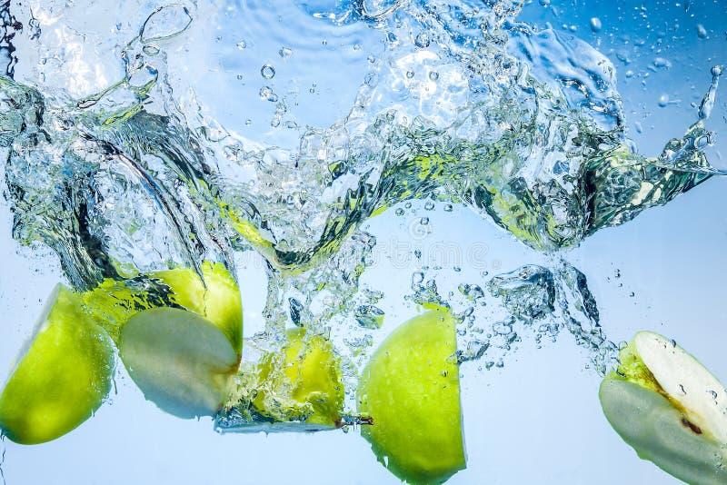 Gröna äpplen. Frukter faller djupt under vatten med färgstänk arkivfoto