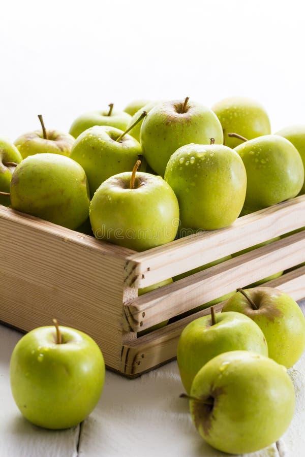 Gröna äpplen i spjällådaslut upp på vit bakgrund med selectiv fotografering för bildbyråer