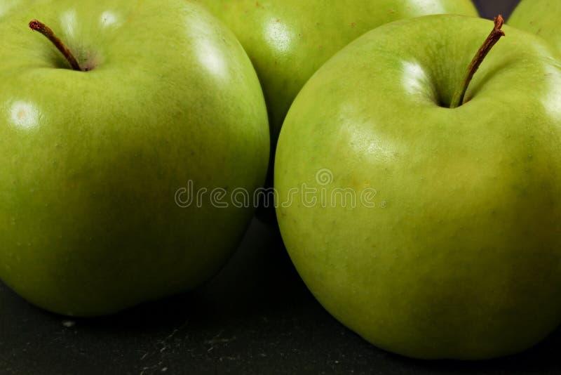 Gröna äpplen på det svarta brädet - closeupfoto med detaljen på hudtextur fotografering för bildbyråer