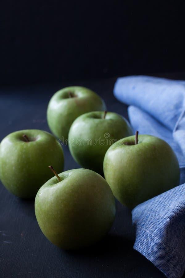 Gröna äpplen på en svart bakgrund arkivbild