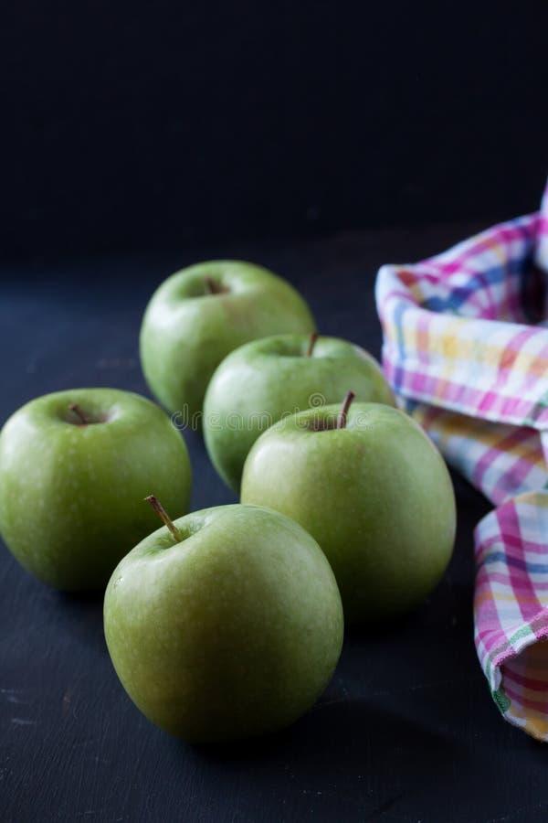 Gröna äpplen på en svart bakgrund arkivfoto