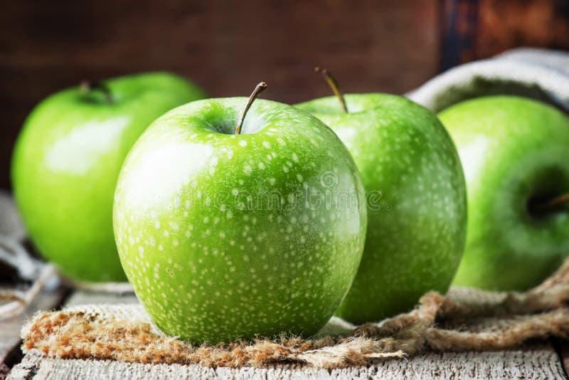 Gröna äpplen på tappningträbakgrund, selektiv fokus arkivfoton