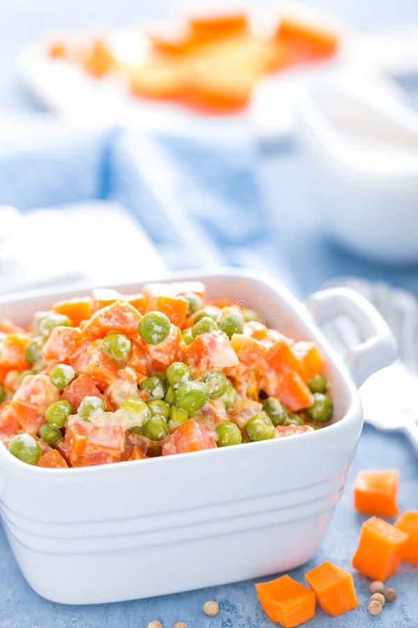 Gröna ärtor lät småkoka med morötter i krämigt mjölkar vit sås royaltyfria foton