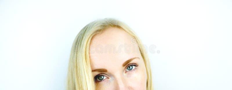 Gröna ögon av en härlig flicka Vit bakgrund Blonda fräknar fotografering för bildbyråer