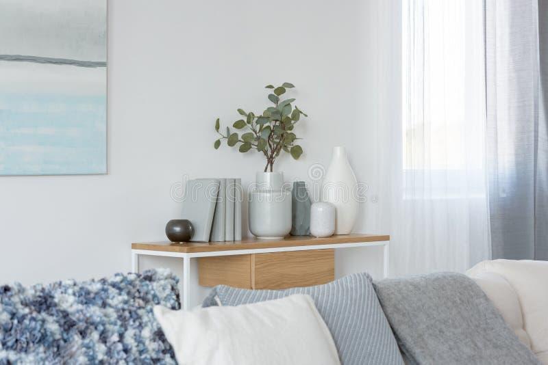 Gröna blommor i grå vas bredvid böcker på träkonsoltabellen i ljus vardagsruminre royaltyfria bilder