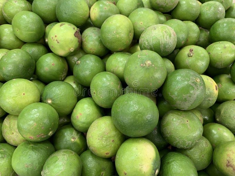Gröna citroner som säljer i marknaden royaltyfri foto