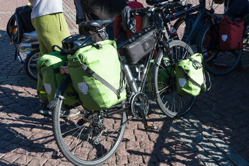 Gröna cykelpåsar för långa resor på bakgrunden av stenläggningstenar royaltyfri fotografi