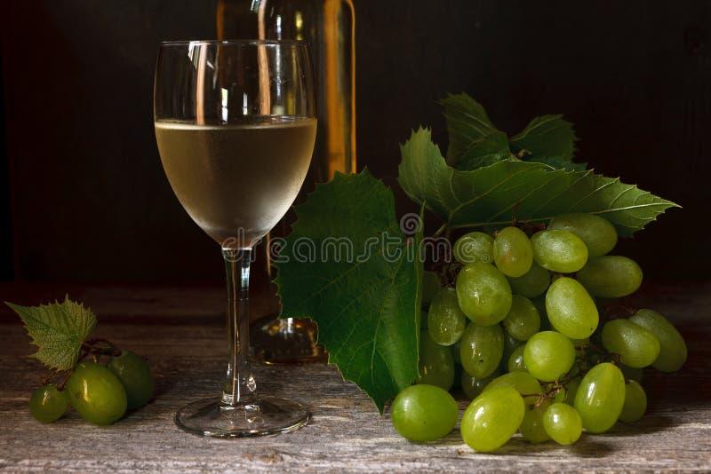 Gröna druvor med sidor, exponeringsglas, flaska av vitt vin på tappning arkivbilder