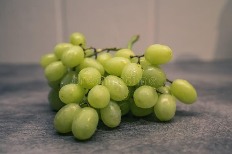 Gröna druvor på räknare arkivfoto