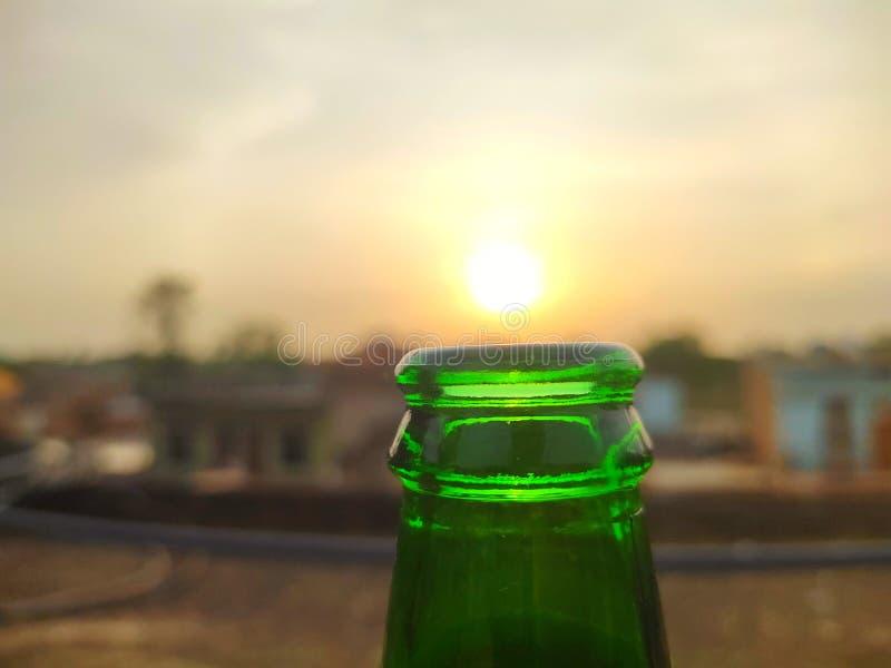 Gröna glasflaskor av öl på solnedgånghimmel tom ?lflaska royaltyfria bilder