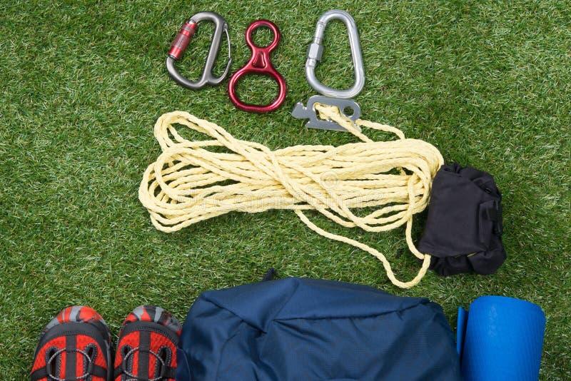 gröna gräsmattalögnobjekt för att klättra i berg, en grupp av rep, en uppsättning av karbiner, en ryggsäck och skor arkivfoton
