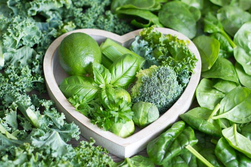 Gröna grönsaker och örter i hjärtahälsobegrepp arkivbild