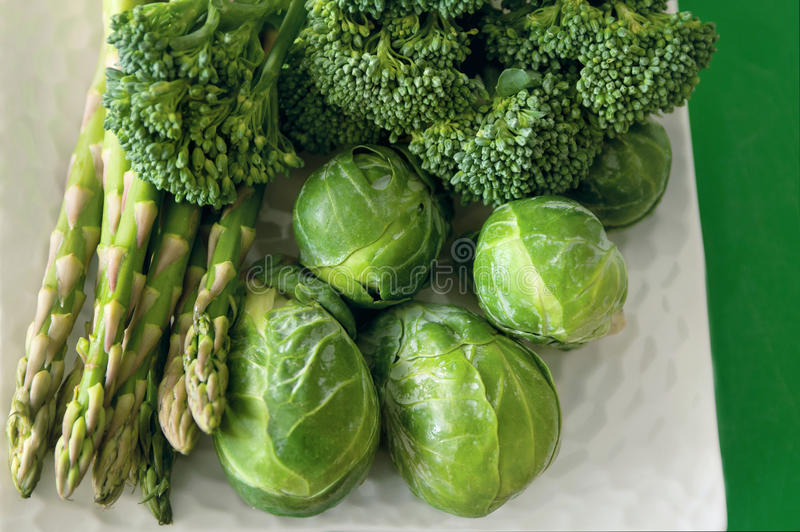 Gröna grönsaker på den vita plattan royaltyfri bild