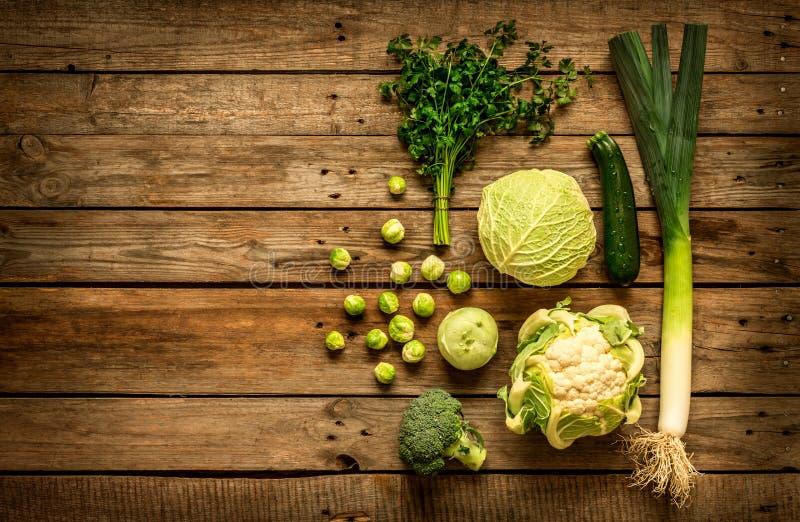 Gröna grönsaker på lantlig träbakgrund för tappning arkivfoton