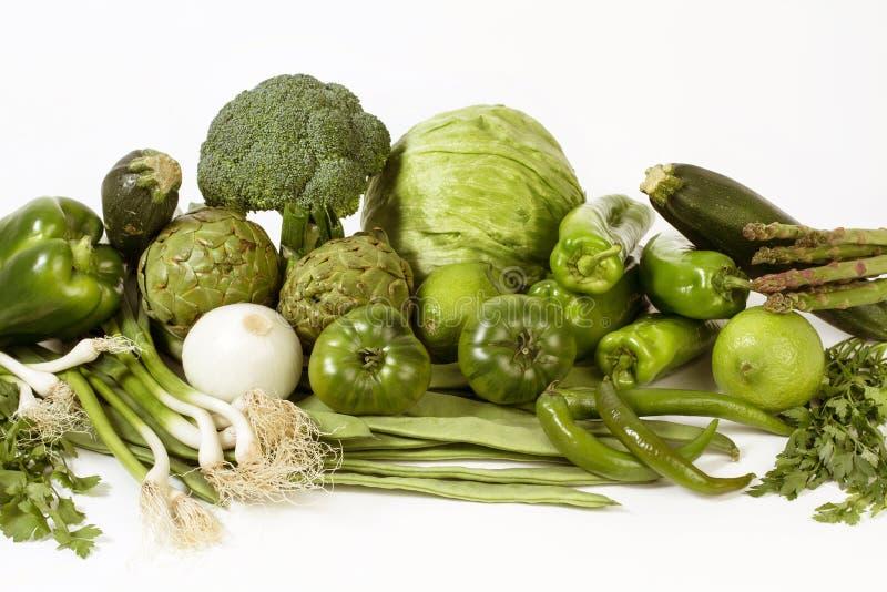 Gröna grönsaker som gör en sallad på vita bakgrunder arkivfoton